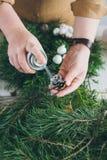 做圣诞节花圈的卖花人装饰员 免版税库存图片