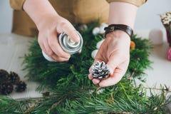 做圣诞节花圈的卖花人装饰员 免版税库存照片