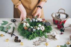 做圣诞节花圈的卖花人装饰员 免版税图库摄影