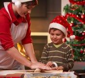 做圣诞节蛋糕的母亲和儿子 库存图片