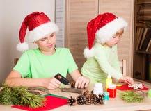 做圣诞节装饰的孩子 做圣诞装饰 库存照片