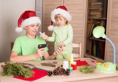 做圣诞节装饰的孩子 做圣诞装饰 免版税库存图片