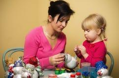 做圣诞节装饰的母亲和女儿 免版税库存照片