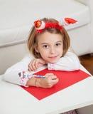 做圣诞节贺卡的女孩 免版税库存照片