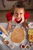 做圣诞节主题的曲奇饼的现代主妇在厨房里 免版税库存图片