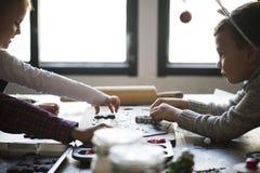 做圣诞节DIY项目的孩子 免版税库存照片