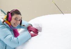 做在一个多雪的车窗的逗人喜爱的妇女驱动器一个漏洞 免版税图库摄影