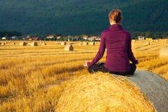 做在一个大包的女孩瑜伽在早晨太阳的干草 免版税图库摄影