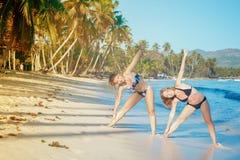 做在一个热带海滩的两个女孩体育运动 库存图片
