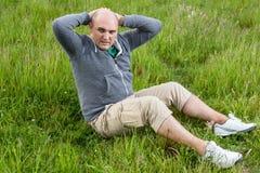 做在一个绿色草甸的人仰卧起坐 免版税库存照片