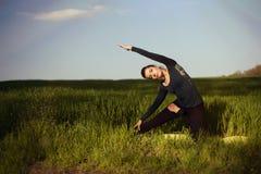 做在一块麦田的美丽的年轻深色的妇女瑜伽联合国 免版税库存图片