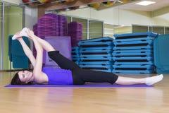 做在一张席子的适合的妇女瑜伽锻炼在健身房 免版税图库摄影