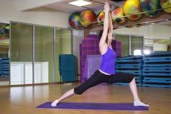 做在一张席子的适合的妇女瑜伽锻炼在健身房 免版税库存图片