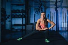 做在一张锻炼席子的五颜六色的运动服的适合的妇女burpees在一个脏的工业类型空间 库存图片