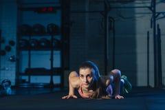 做在一张锻炼席子的五颜六色的运动服的适合的妇女burpees在一个脏的工业类型空间 库存照片