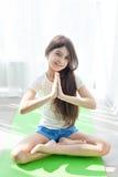 做在一张绿色瑜伽席子的小女孩体操在莲花坐 免版税库存照片