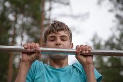 做在一架单杠的少年锻炼 免版税库存图片