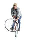做在一辆自行车的年轻人把戏在白色 免版税库存照片