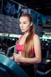 做在一辆踏车的健身妇女连续exerciseon在健身俱乐部 图库摄影