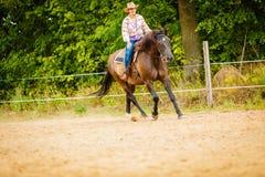 做在乡下草甸的女牛仔马骑术 库存图片