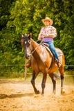 做在乡下草甸的女牛仔马骑术 免版税库存照片