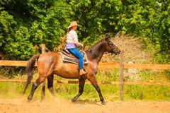 做在乡下草甸的女牛仔马骑术 图库摄影