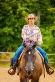 做在乡下草甸的女牛仔马骑术 免版税图库摄影