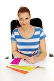 做在书桌后的少年妇女家庭作业 库存图片