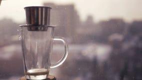 做在亚洲人的新鲜的咖啡,咖啡下落在一个透明杯子下降以一个模糊的城市为背景 库存照片