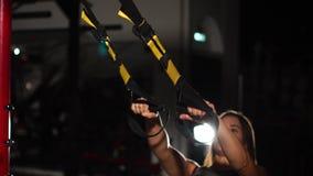 做在体操圆环的年轻人适合的妇女引体向上 行使与圆环的肌肉年轻女运动员在健身房 股票录像