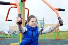 做在体育模拟器的小女孩锻炼在运动场 免版税库存图片