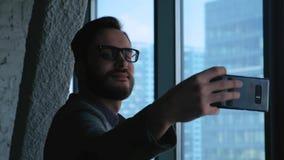 做在俯视街市的窗口的背景的年轻成功的商人selfie 高大厦的商业 股票录像