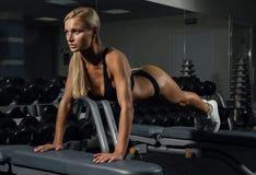 做在健身俱乐部的美丽的女孩锻炼在长凳 库存图片