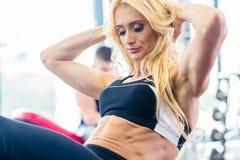 做在健身健身房的体型妇女仰卧起坐 免版税图库摄影