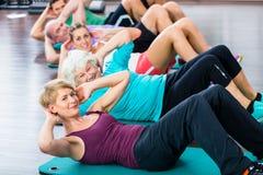 做在健身健身房的资深和青年人仰卧起坐 免版税库存照片