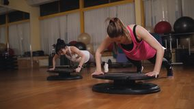 做在健身房的两名妇女有氧运动使用平衡板 股票录像