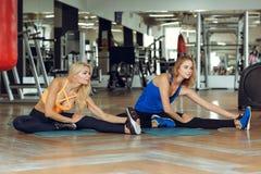 做在健身房的两名年轻苗条白肤金发的妇女锻炼 库存照片