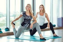 做在健身房的两名年轻苗条白肤金发的妇女锻炼 免版税图库摄影