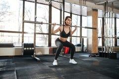 做在健身房的健身妇女蹲坐锻炼 免版税库存图片