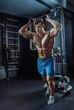 做在健身房的坚强的肌肉爱好健美者锻炼 一部分的健身身体 免版税库存图片