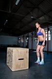 做在健身房的女性一个箱子跃迁 免版税库存照片