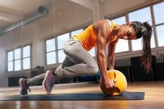 做在健身房的妇女强烈的核心锻炼 库存照片