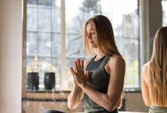 做在健身房的妇女瑜伽锻炼,体育健身女孩坐的莲花姿势 免版税库存图片