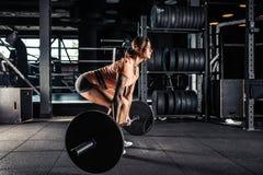 做在健身房的妇女重的deadlift锻炼 免版税库存照片