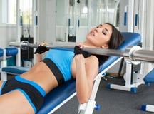 做在健身房的妇女锻炼练习轻的举重 心理调整 炫耀营养 免版税库存照片
