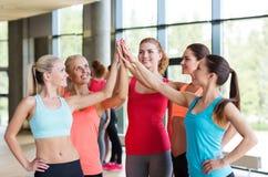 做在健身房的小组妇女上流五姿态 库存图片