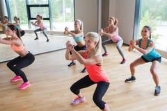做在健身房的小组妇女蹲坐 库存照片