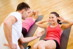 做在健身房的小组微笑的妇女仰卧起坐 库存图片