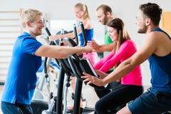做在健身房的小组男人和妇女心脏训练 图库摄影