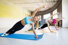 做在健身房的年轻人适合的妇女旁边板条 免版税库存照片
